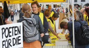 Reges Interesse am Unterschriftenlistentisch von Amnesty International. In den Vordergrund gehalten wird hier ein Schild mit der Aufschrift »Poeten für die Menschenrechte«. Foto: Jan-Eike Hornauer